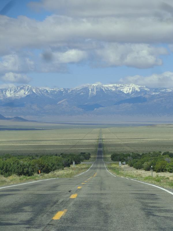 A lonely Nevada road: long, straight, silent, and empty, leading towards the snowcapped mountains in the West.